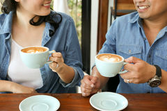 Smiling Asian couple in blue jean shirt having hot heart latte art coffee Stock Photos