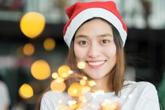 Smiling asia woman wear santa hat holding party string lights wi. Th bokeh light at Christmas party,Holiday celebration concept,sparkling light decoration,make a Royalty Free Stock Photos