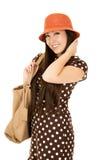 Smiling Asian American teen girl wearing brown polka dot dress Stock Photos