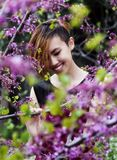 Smiling Asian American Woman Amid Spring Purple Blossoms Royalty Free Stock Photography