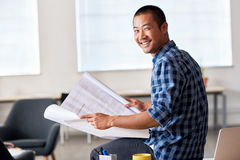 Smiling Asian architect reading blueprints in an office. Portrait of a casually dressed young Asian architect smiling confidently while reading blueprints in a Royalty Free Stock Photo