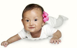 Smiling Asian Baby. On her stomach on the mattress stock image