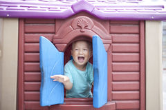 Smiling asian baby boy head out of plastic window Stock Photography