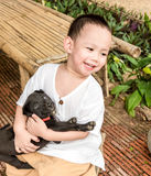 Smiling Asian baby boy hug little black dog in arm Royalty Free Stock Photography