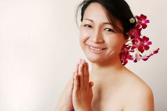 Smiling asian beauty with orchids royalty free stock images