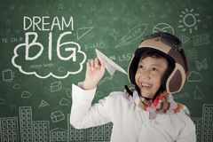 Smiling Asian boy wearing helmet holding a plane paper Royalty Free Stock Images