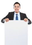 Smiling asian business man holding empty board Royalty Free Stock Photos
