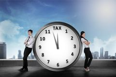Smiling asian business team lean back on the clock with tax sign. Goods and Services Tax concept Stock Photography