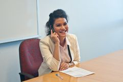Business woman call to inquire more details and talk. Smiling Asian business woman calls to inquire more details and talk over phone Royalty Free Stock Image