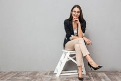 Smiling asian business woman in eyeglasses sitting on chair. And looking at the camera over gray background stock photos