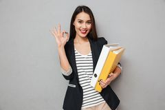 Smiling asian business woman holding folders and showing ok sign. While looking at the camera over gray background Stock Photography