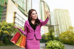 Smiling asian business woman selfie with holding shopping bags Stock Images