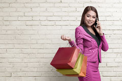 Smiling asian business woman with shopping bags using her smartp Royalty Free Stock Photography