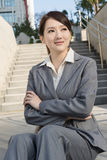 Smiling Asian business woman sit on stair Royalty Free Stock Photos