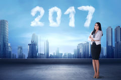 Smiling asian business woman standing beside cloud shaped number. 2017 at the sky Stock Image