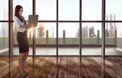 Smiling asian business woman typing while holding laptop Royalty Free Stock Image