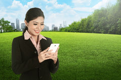 A Smiling asian business woman using cellphone Stock Photography