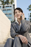 Smiling Asian business woman using cellphone and sit on stairs a Stock Images