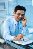 Smiling asian businessman calling someone. In office royalty free stock photos