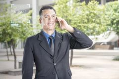 Smiling asian businessman with mobile phone using face recognition. Over outdoor background. Modern technology concept stock photography