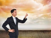 Smiling asian businessman pointing Stock Photos