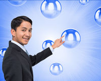 Smiling asian businessman pointing Stock Image