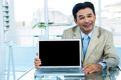 Smiling asian businessman showing laptop. In office stock photos