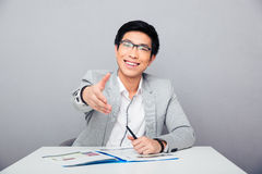 Smiling asian businessman stretching hand for handshake Stock Photography