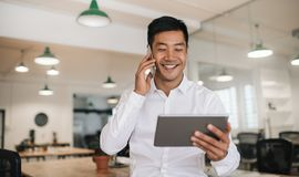 Smiling Asian businessman using a cellphone and tablet at work Royalty Free Stock Photos