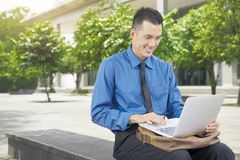 Smiling asian businessman using laptop Stock Photography