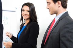 Smiling Asian businesswoman beside Caucasian businessman Stock Photo