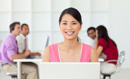 Smiling asian businesswoman at her computer Stock Image