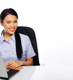 Smiling Asian businesswoman at her desk Stock Images