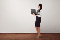 Smiling asian businesswoman holding laptop while standing Royalty Free Stock Photography