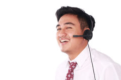 Smiling Asian Call Center Operator. Photo image portrait of a cute young Asian male call center operator with headset on his head isolated on white Royalty Free Stock Photography
