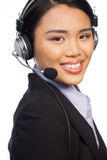 Smiling Asian call centre telephonist. Or help desk operator wearing a set of headphones and microphone isolated on white Royalty Free Stock Photos