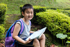 Smiling Asian Chinese boy holding map sitting in the forest Royalty Free Stock Photography