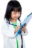 Smiling Asian Chinese Little Doctor Writting On Clip Board Royalty Free Stock Images