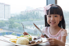 Free Smiling Asian Chinese Little Girl Eating Lamb Steak With Rice Stock Photography - 89305642