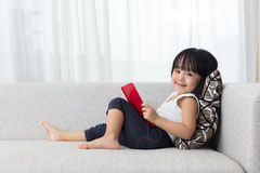 Smiling Asian Chinese little girl reading book on the sofa Royalty Free Stock Images