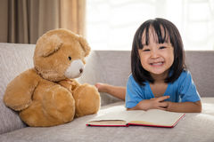Smiling Asian Chinese little girl reading book with teddy bear Royalty Free Stock Photos