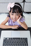 Smiling Asian Chinese little girl using laptop at home Stock Photo