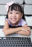 Smiling Asian Chinese little girl using laptop at home Royalty Free Stock Photos