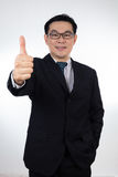 Smiling Asian Chinese man wearing suit posing with thumbs up Royalty Free Stock Images