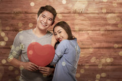 Smiling asian couple in love holding red heart symbol. Against wooden plank background Royalty Free Stock Photography