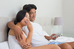 Smiling asian couple lying on bed watching tv. At home in bedroom Royalty Free Stock Photos