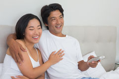 Smiling asian couple lying on bed watching tv Royalty Free Stock Photos