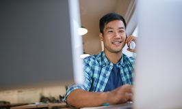 Smiling Asian designer working at his desk in an office Stock Photos