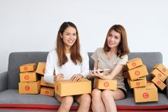 Smiling Asian entrepreneur owner women with cardboard box sitting on modern sofa at home. Online start up business.  stock images