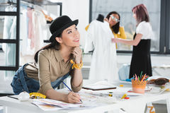 Smiling asian fashion designer drawing sketches while colleagues working behind. Young smiling asian fashion designer drawing sketches while colleagues working Royalty Free Stock Image